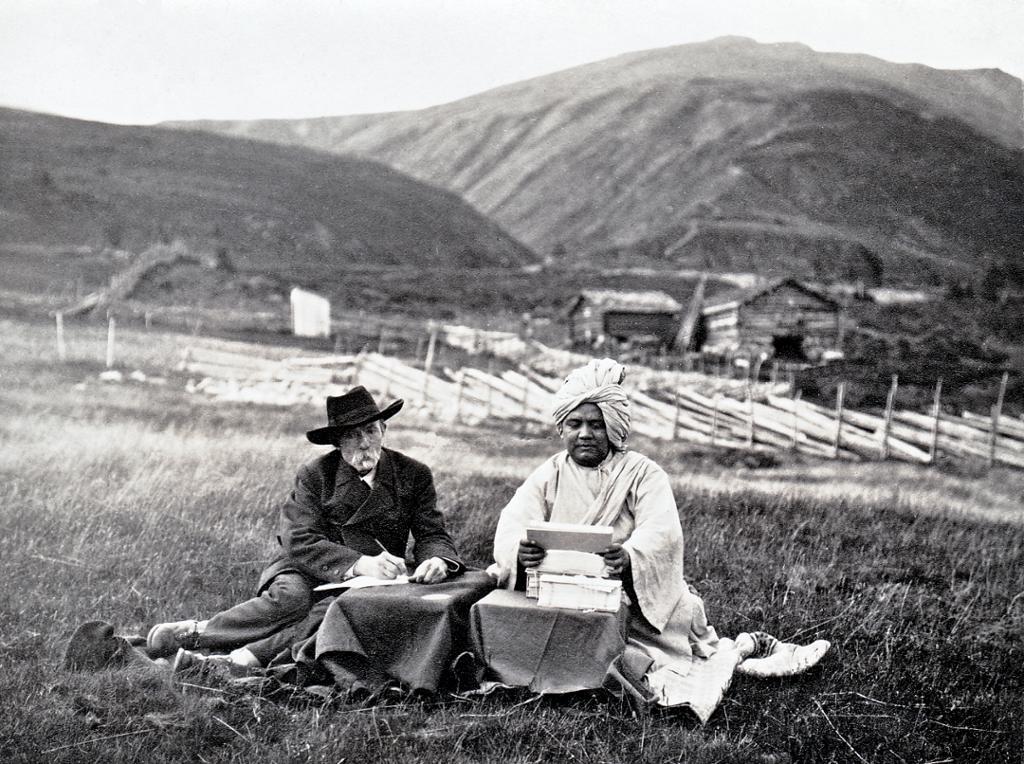 En mann med svart dress og hatt og en mann med turban sitter sammen i gresset ved hvert sitt lille bord. Mannen med hatten skriver og mannen med turbanen leser. I bakgrunnen er det fjell, seterbygninger og en skigard. Svart-hvitt. Foto.