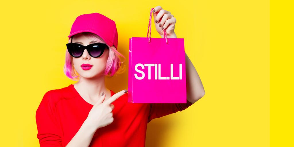 Dame med kule solbriler holder en handlepose fra Stil.li. Foto.