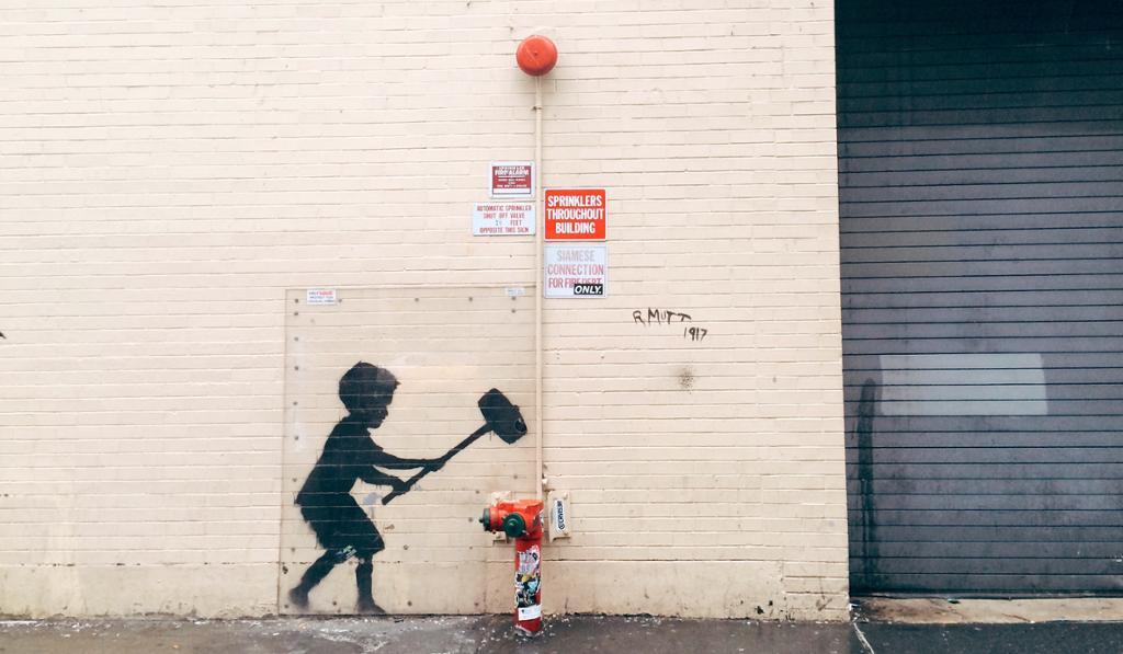 Gatemaleri på murvegg av gutt som slåt med slegge på en brannhydrant. Foto.
