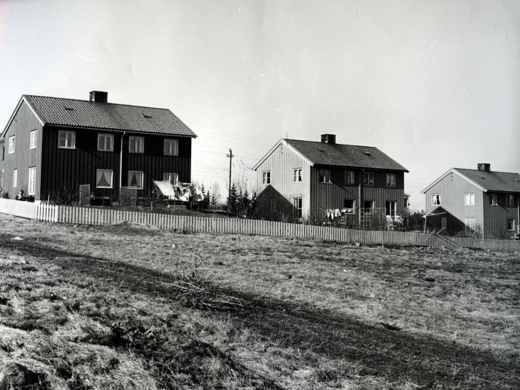 Boliger, kalt både svenskehus og Jøtulbygga, ved et jorde på Manglerud, ca 1954. Foto.