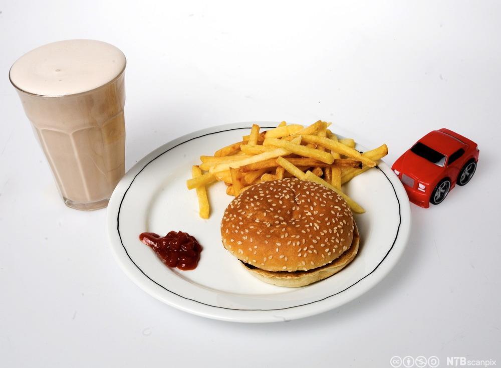 Bilde av en tallerken med hamburger og pommes frites, og en liten bil ved siden av. Foto.