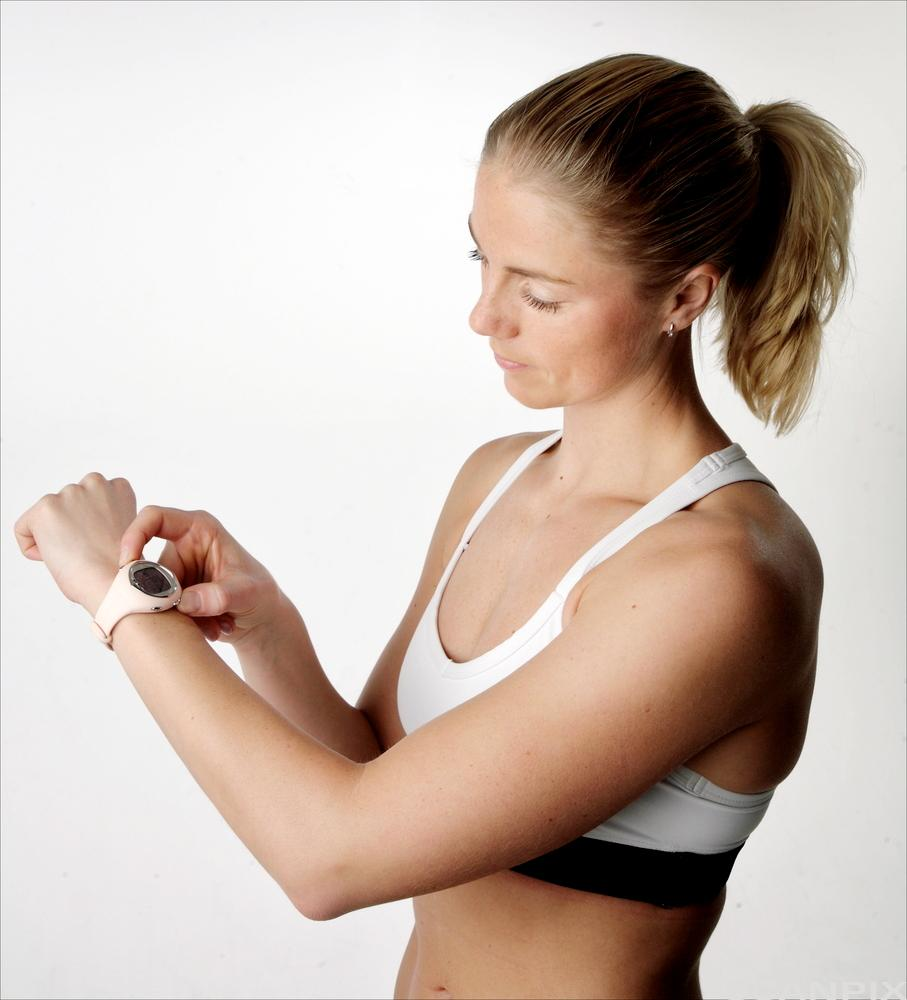 Kvinne i treningstøy sjekker pulsklokke. Foto.