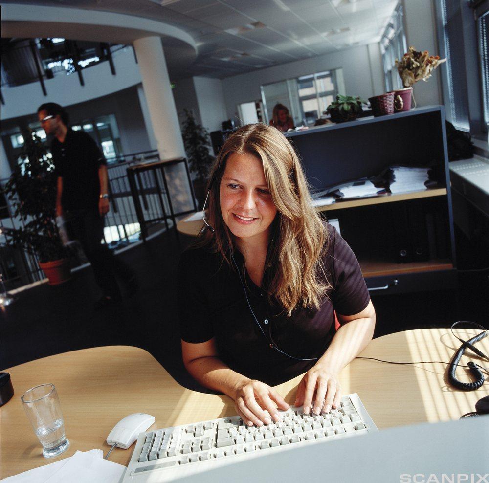 Kvinne som sitter foran datamaskin på et kontor. Foto