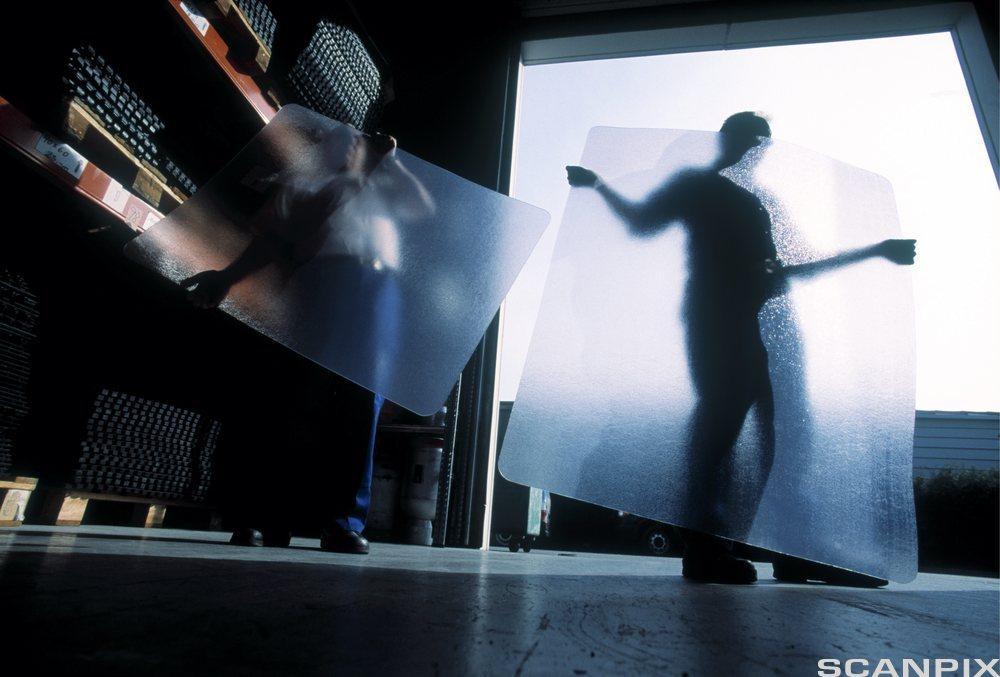 Mann legger plastunderlag til kontorstol. Foto.