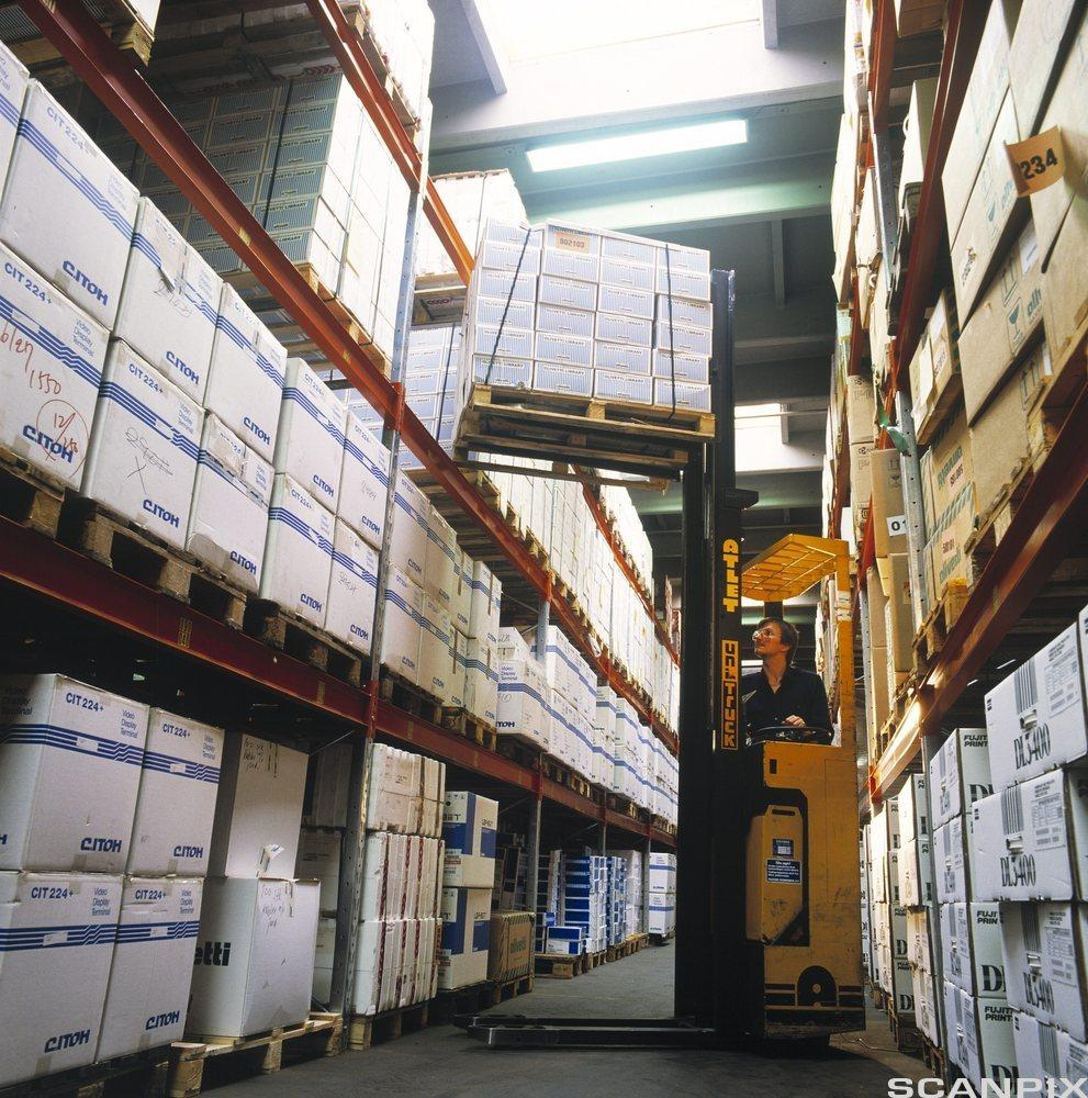 Gaffeltruck løfter paller inne på et lager. Foto.