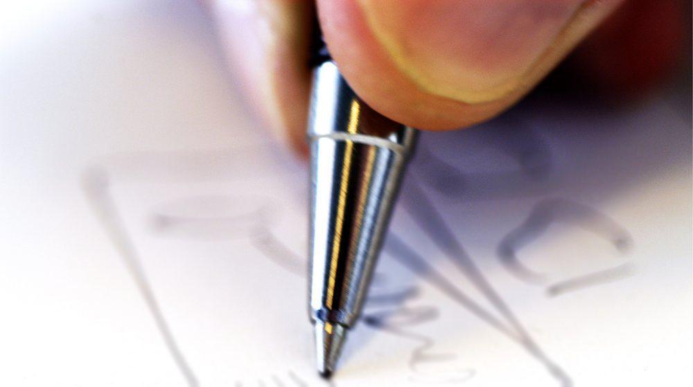 Fingre som skriver med penn på papri. Foto.