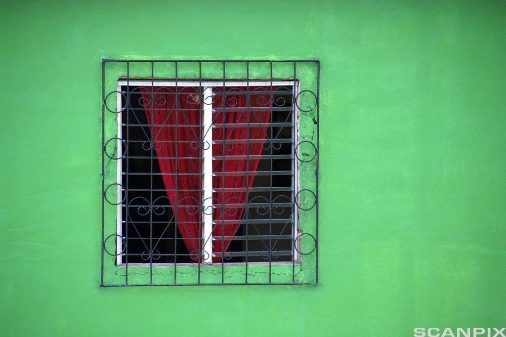 Vindu med rød gardin på grønn vegg. Foto.