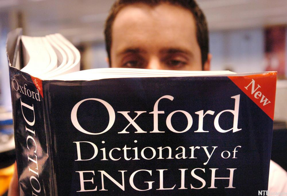 Man reading in Oxford Dictionary of English. Photo.