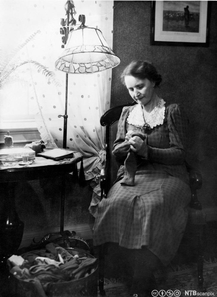 En eldre kvinne sitter og stopper strømper under en stålampe. Foto.