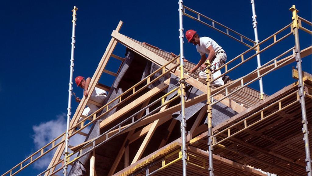 Hustak og stillas med tømrere i arbeid. Foto.