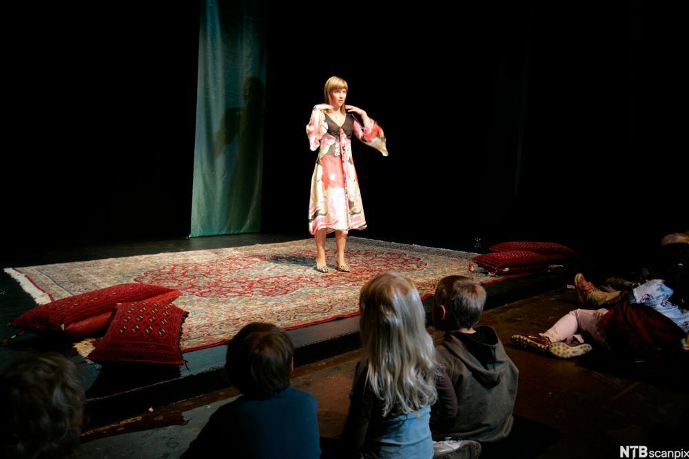 Prinsesse Märtha Louise står på en scene og forteller for barn. Foto.