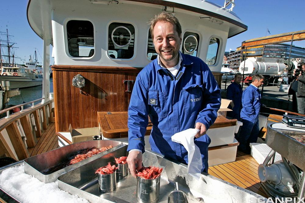 Investor Kjell Inge Røkke selger reker fra brygga. Foto.
