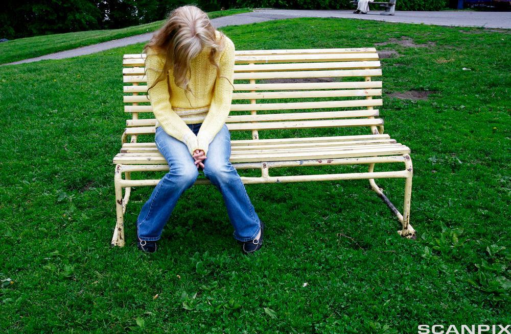 Jenter sitter på en benk og ser ned i bakken. Foto.