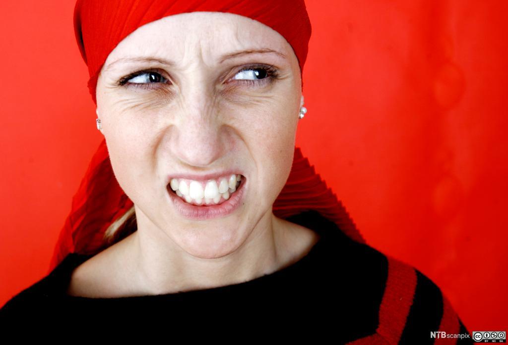 Kvinne med rødt tørkle på hodet som viser sint uttrykk. Foto.