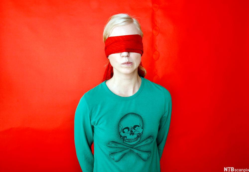 Ung kvinne med bind for augene. Foto.