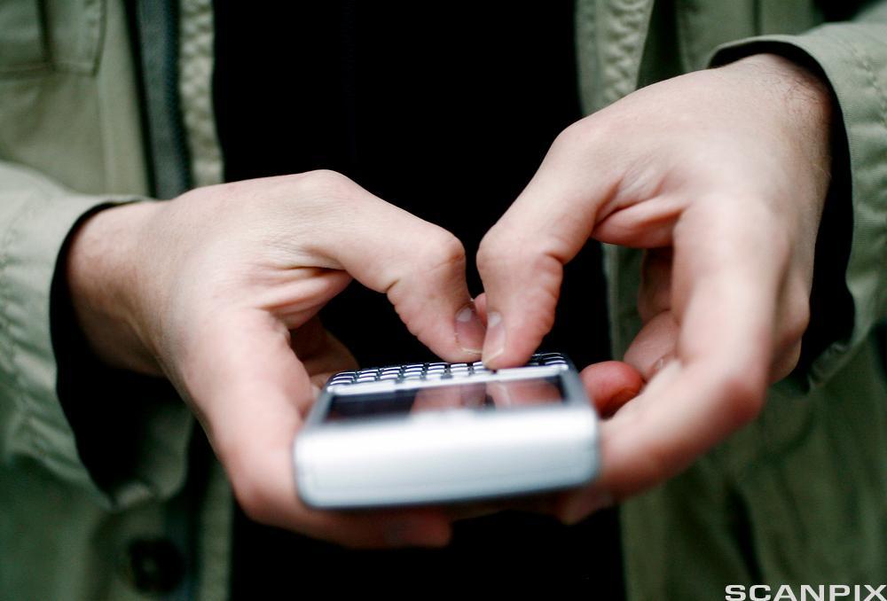Person skriver SMS. Foto.