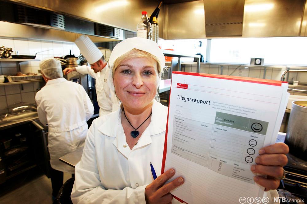 Kokk holder opp en tilsynsrapport fra mattilsynet. Foto.