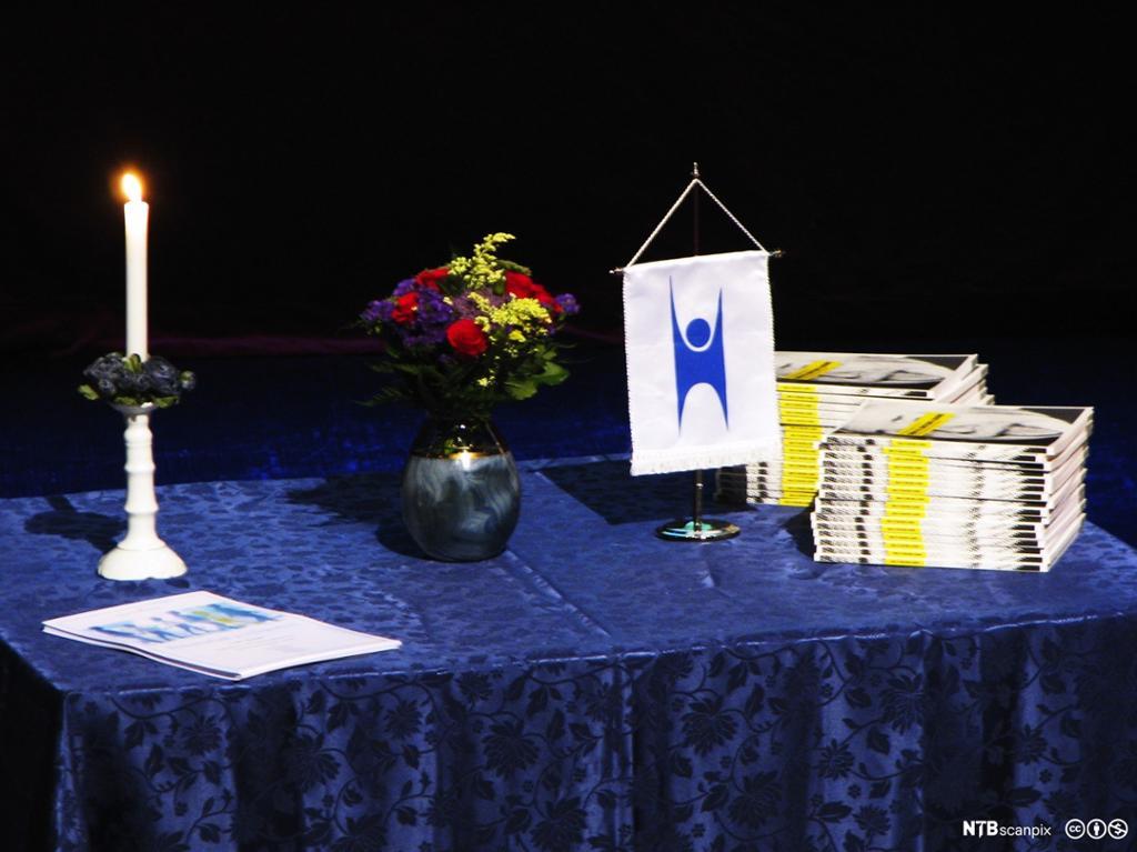 Bord med blå duk, et tent stearinlys og en vinpel med enlogso som fremstiller et menneske. Foto.