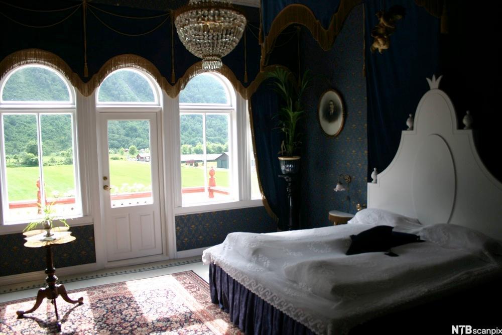 Bilde av et rom ved Hotel Union i Øye. Buede vinduer, lysekrone og romantisk seng. Grøntområde utenfor. Foto.