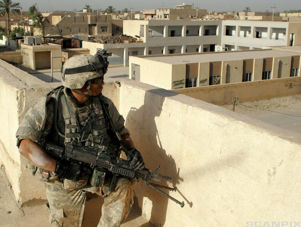 A US soldier looks from a roof top during a mission