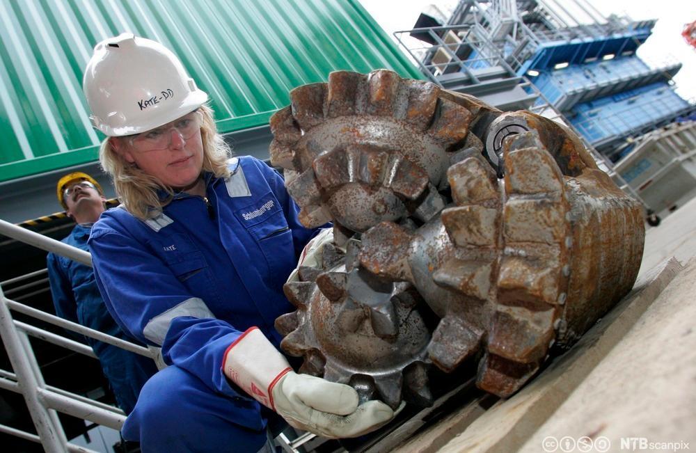 En arbeider håndterer en borkrone av typen «Roller Cone». Foto.
