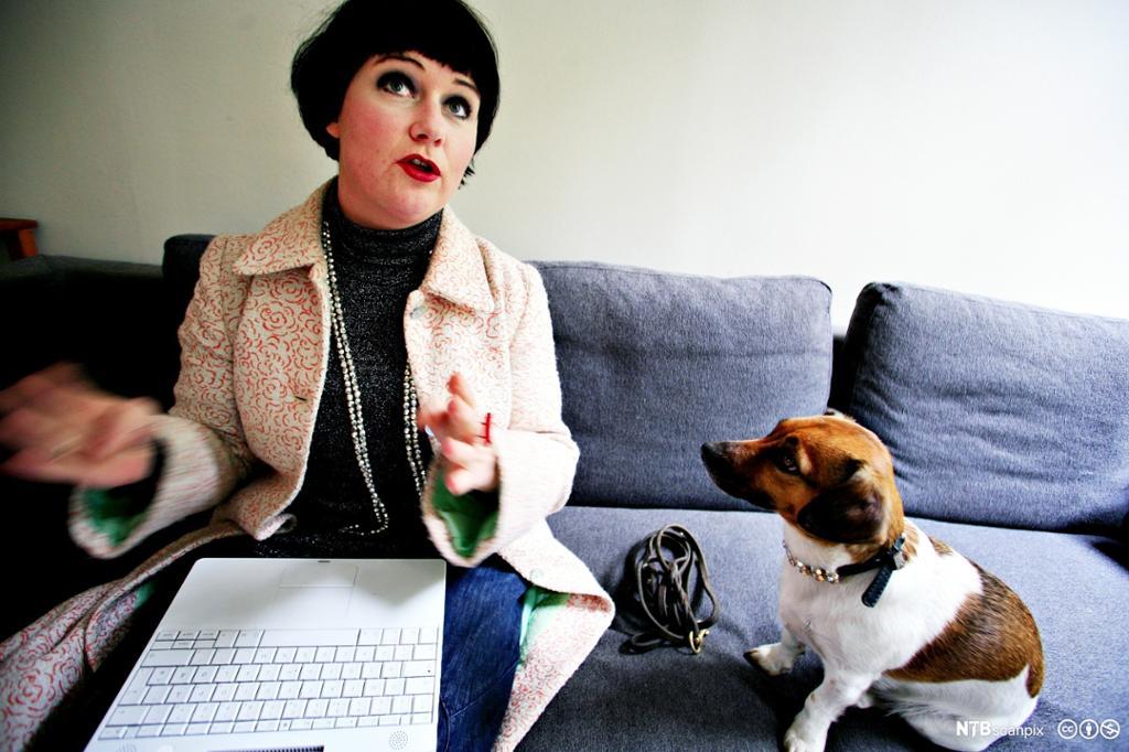 Christine Koht på sofaen hjemme, med laptop i fanget og hunden Pippi ved sida av seg. Foto.
