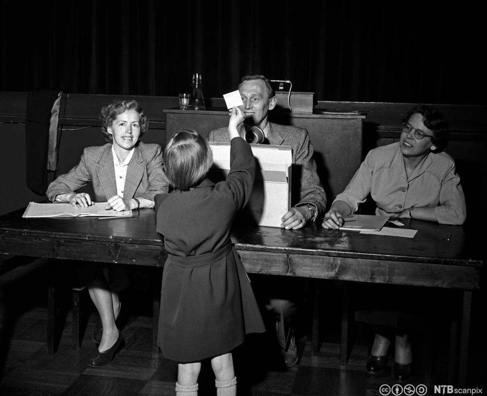 Obos-medlemmer på trekningsmøte for leiligheter i 1955. Bente Mæland trekker en leilighet til seg og foreldrene. Foto.