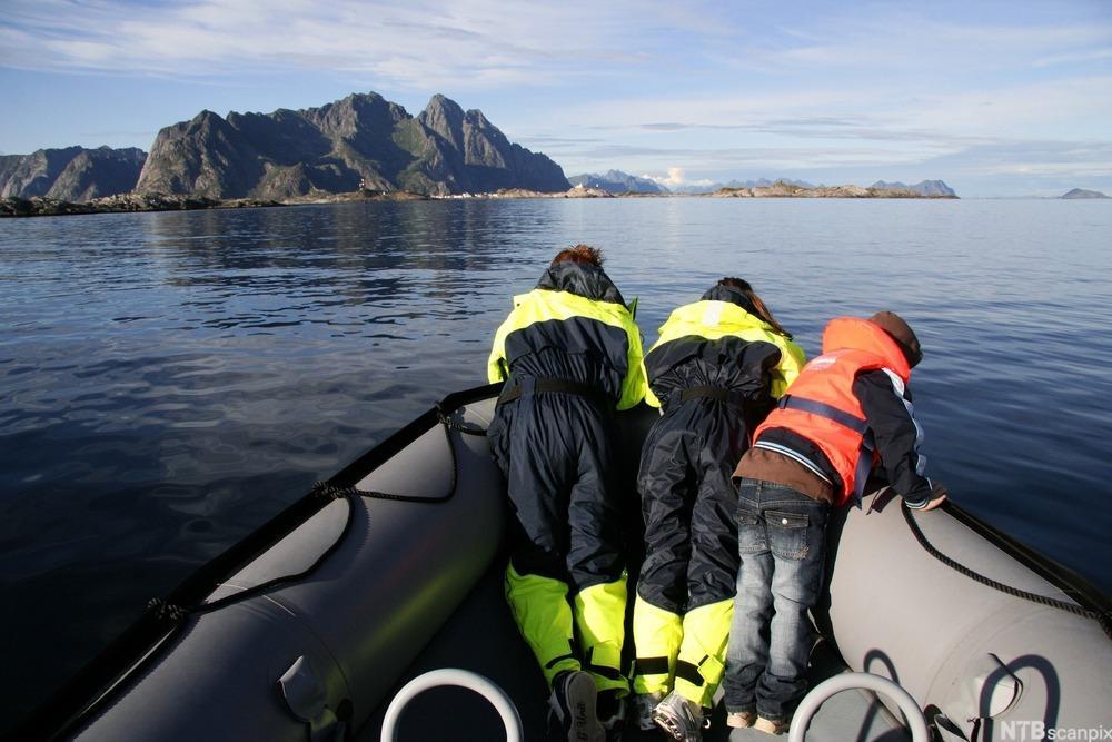 Tre personer i rib i Lofoten. Foto.
