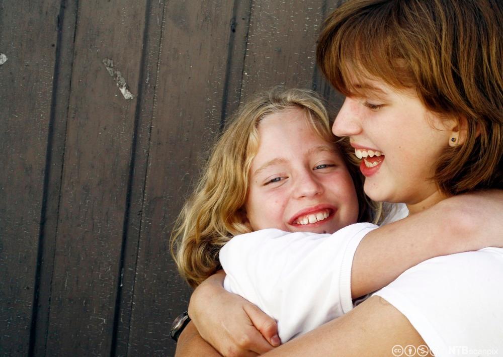 Glade søstre holder rundt hverandre. Foto.