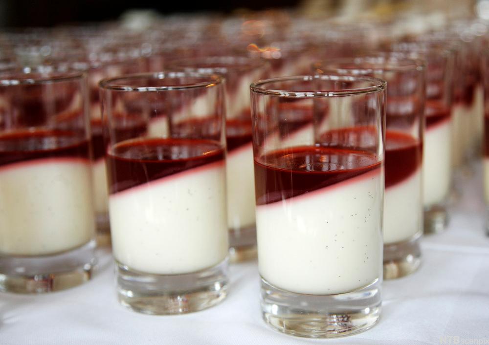 En rekke smale dessertglass står plassert på et bord. I hvert glass er det en lys pudding med rød bærsaus oppå. Foto.