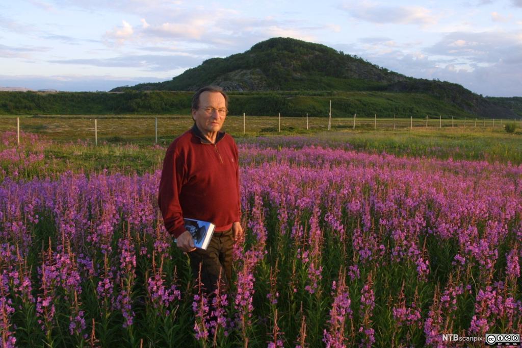 Forfatter med bok i blomstereng. Foto.
