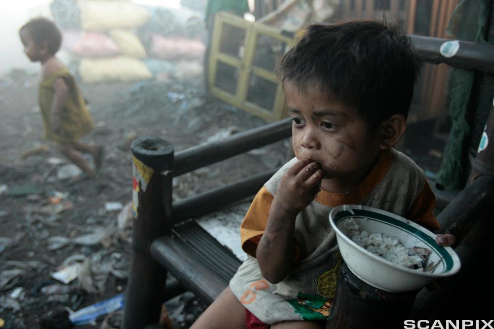Et fattig barn spiser mat. Foto.