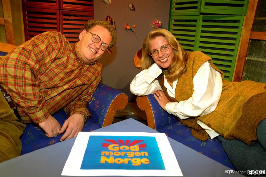 En mann og en dame med logoen til programmet God morgen Norge mellom seg. Foto.