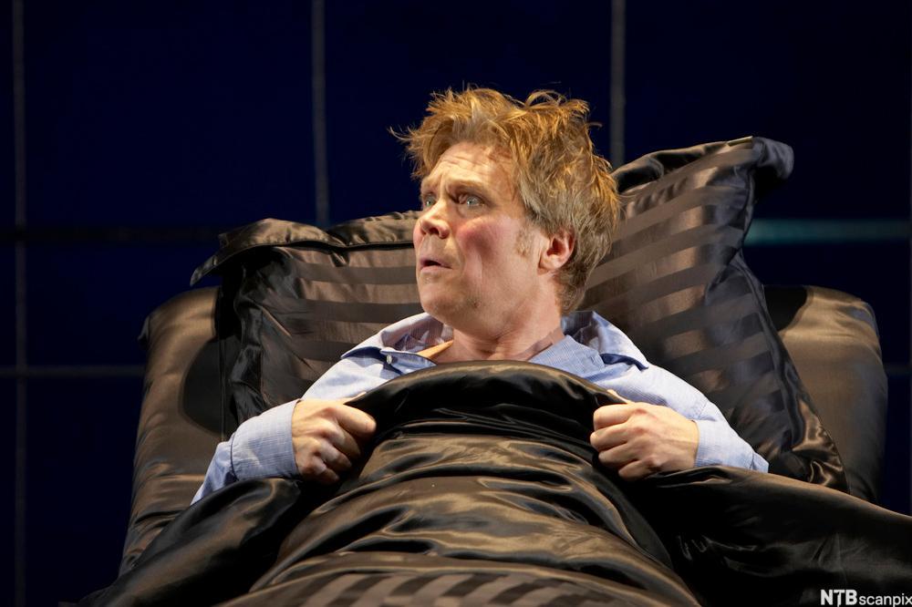 Ein mann ligg i seng med silkelaken. Han stikk hovudet opp og ser heilt forfjamsa ut. Foto.