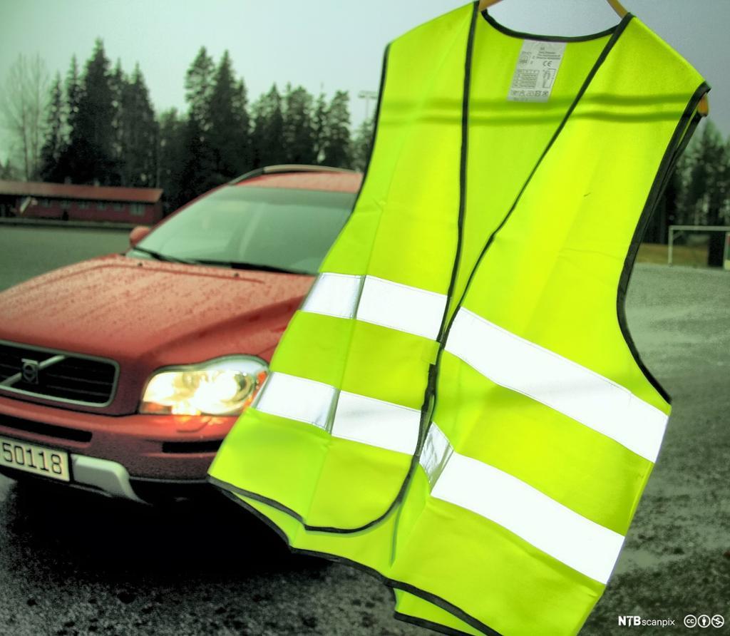 Refleksvest på kleshenger ute, med bil i bakgrunnen. foto.