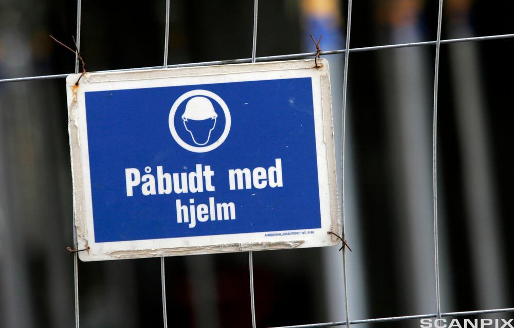 Skilt: påbudt med hjelm. foto.