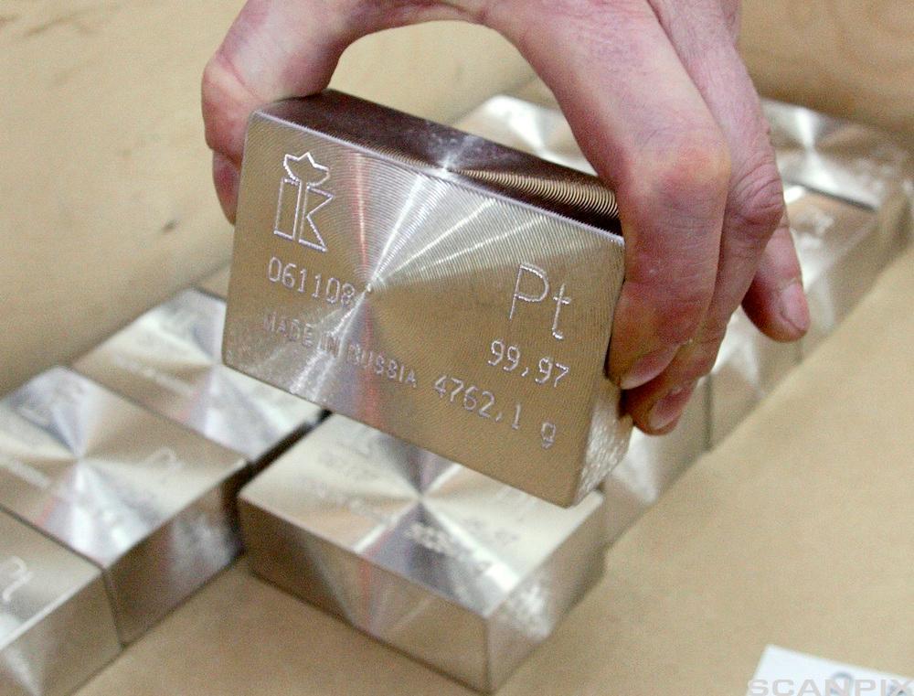 En arbeidstaker setter en ingot av platina inn i en boks. Foto.