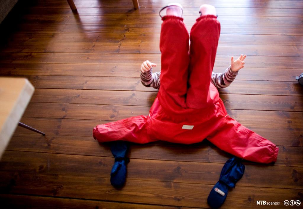 Lite barn som ligger på gulvet og tar på utedress. Foto.