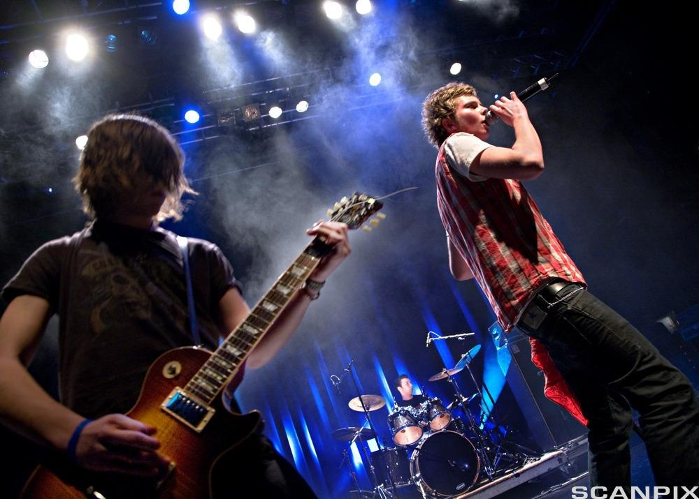 Eit band speler på ein scene. Gitarist og vokalist i forgrunnen, trommis i bakgrunnen. Foto.