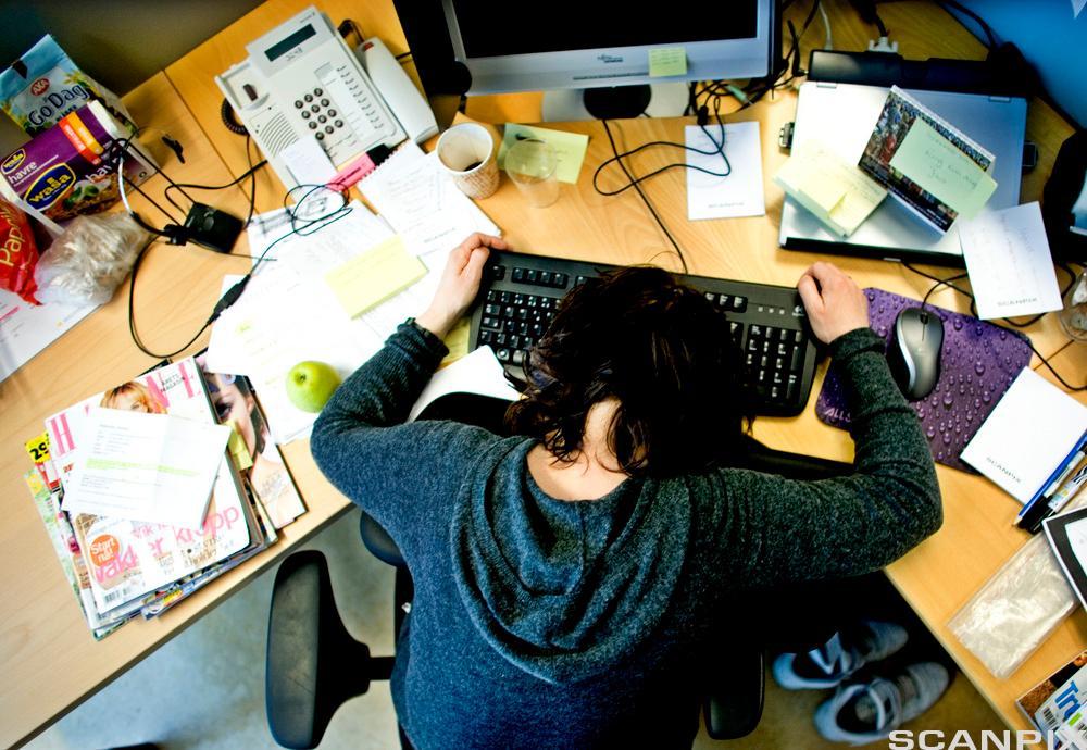 Mann foroverbøyd over et nokså rotete arbeidsbord. Foto.