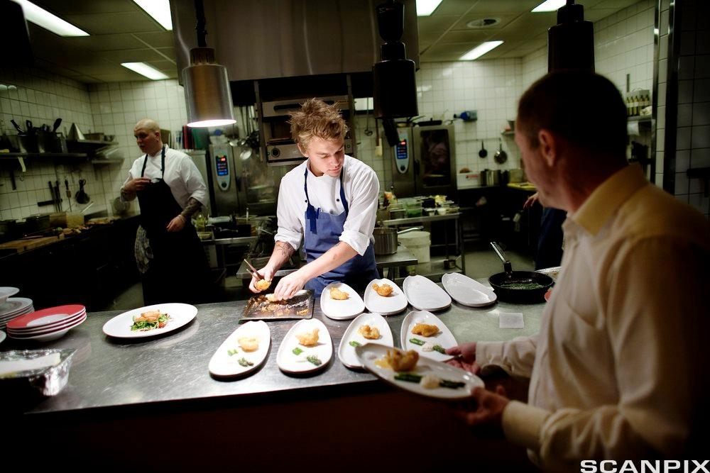 En kokk og en servitør i arbeid på restaurantkjøkken. Foto.