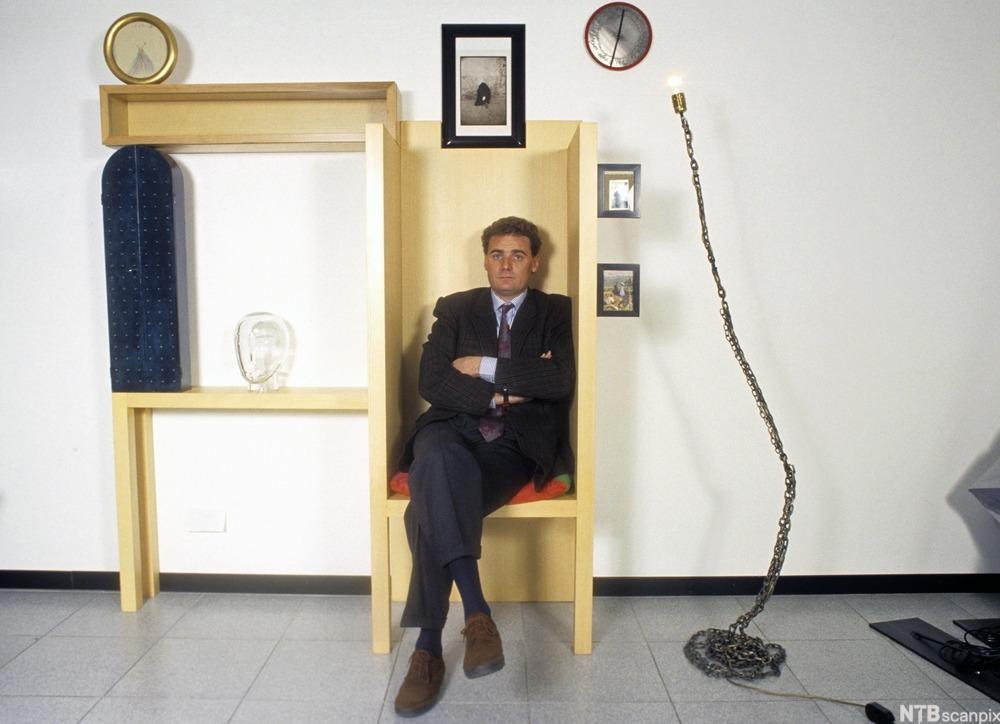 President i Memphis-gruppen sitter på et møbel med postmoderne design. Foto.