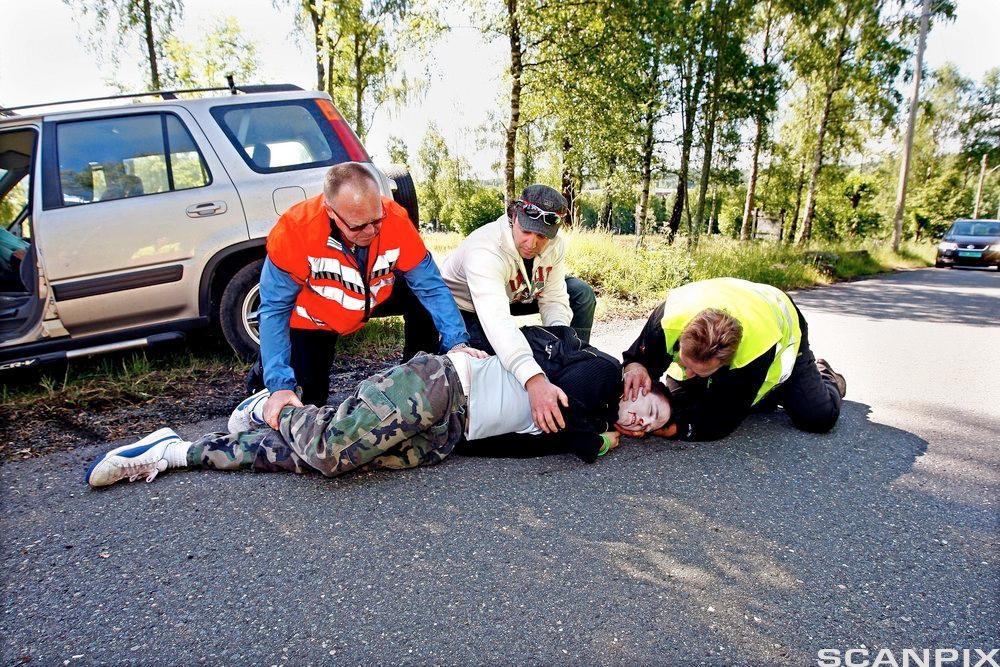 En skadet blir lagt i stabilt sideleie. Foto.