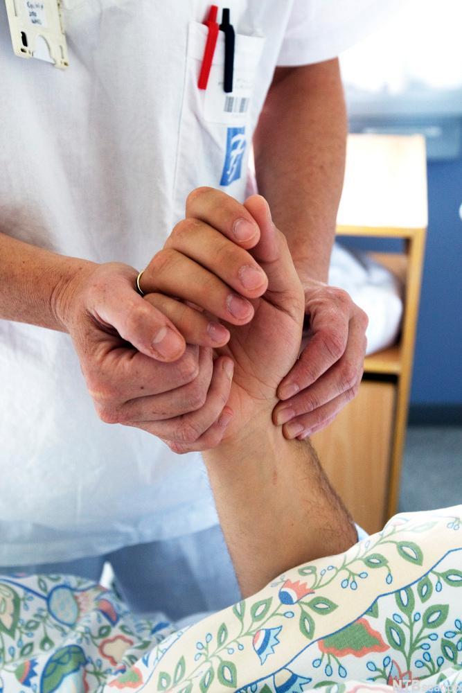 Helsearbeider holder hånda til pasient. Foto.