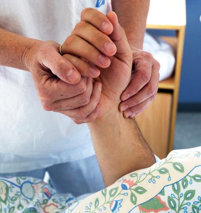 Helsearbeider tar puls på pasient. Foto.