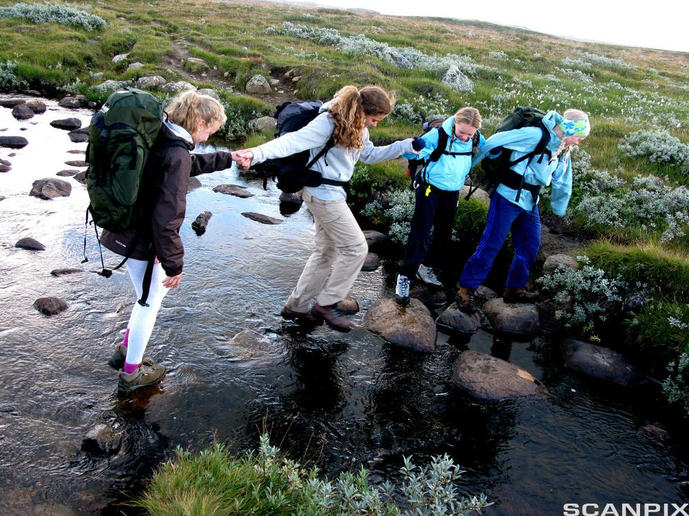 ungdommer på tur over ei elv