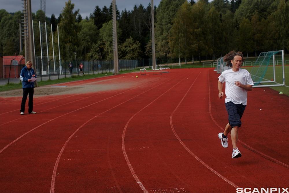 Mann joggar på ein friidrettsbane. Foto.