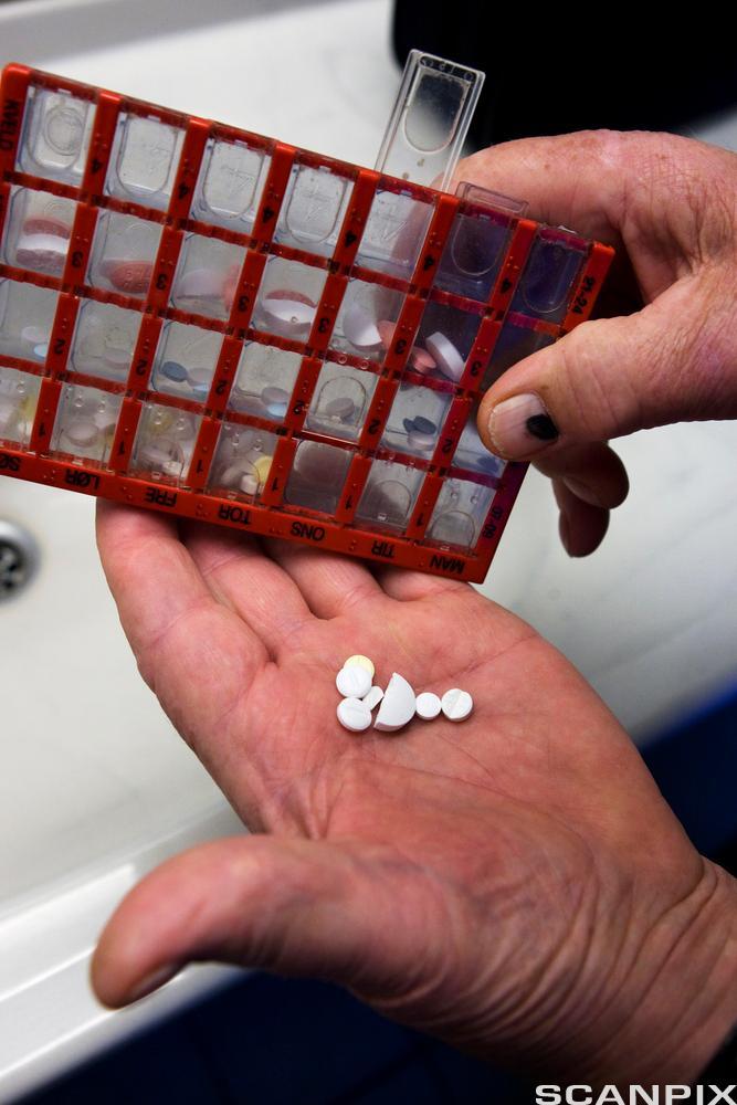 En hand tar ut medisiner fra et medisindosett. Foto.