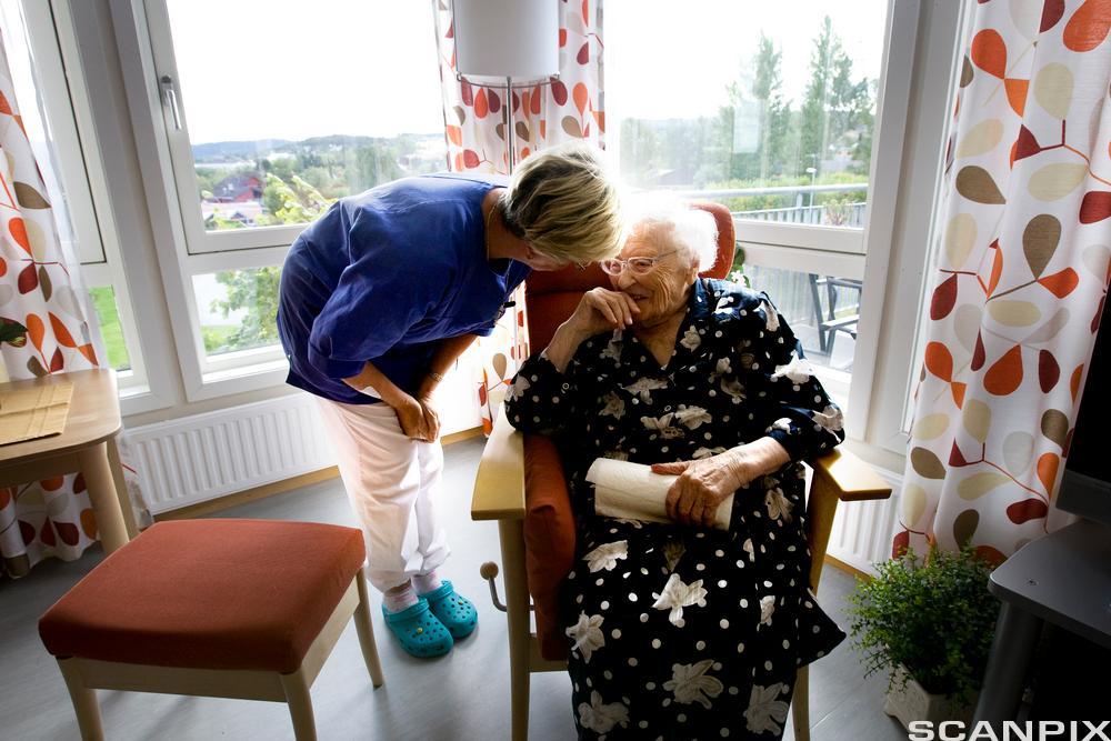 Eldre dame får tilsyn og hjelp fra helsefagarbeider. Foto.