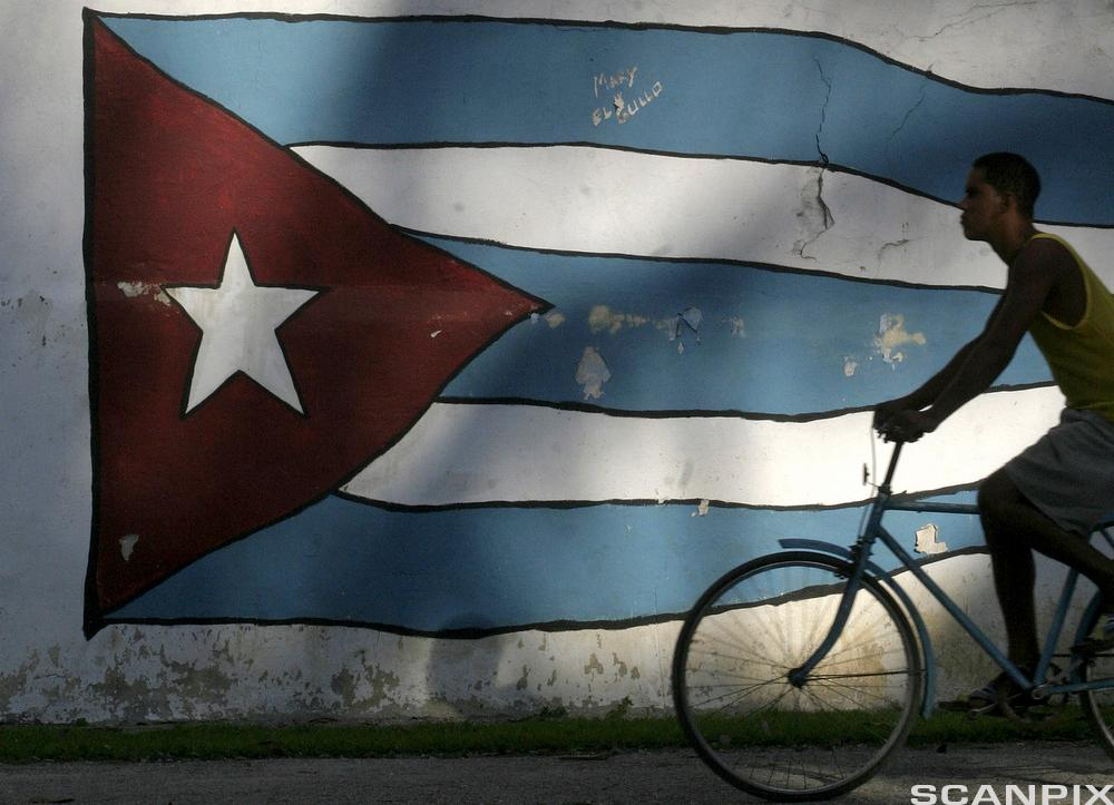 A Man Cycles past a Cuban Flag in Havana